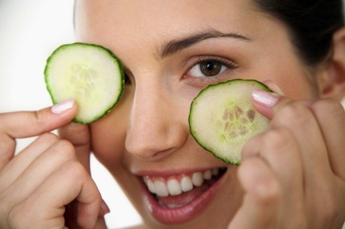 Woman Holding Cucumber Slices over Eyes